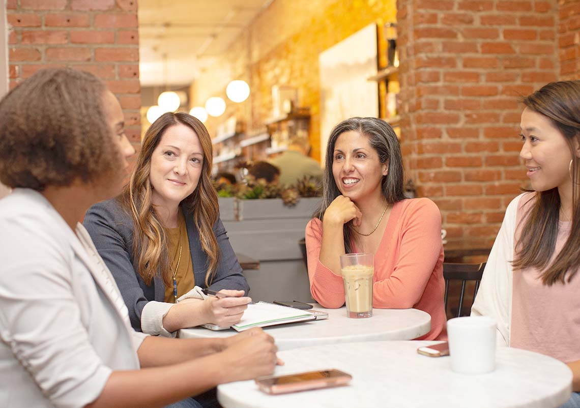 Four professionals sitting around a table talking with each other.