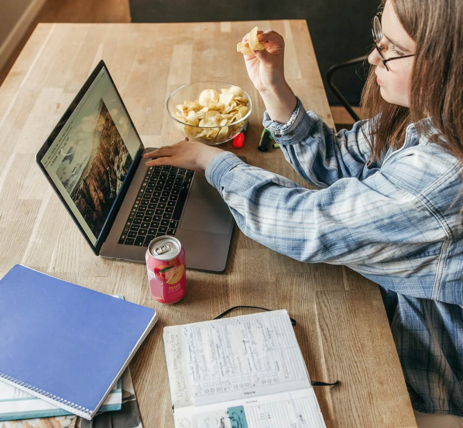 A person studying on a table with books and a laptop while eating a snack.